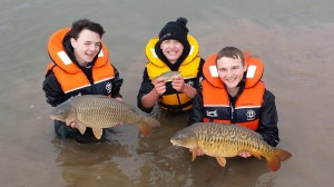 Ryan Richardson and Regan Reynolds hold two large carp while Ben Cook has a smaller roach