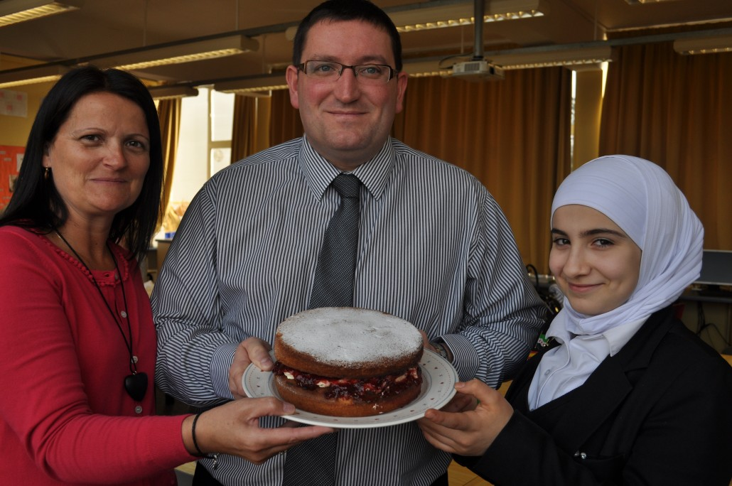 Dia Alwaa shows off her Victoria sponge cake to Nick Blakemore and Reaseheath's Food Training and Communications Co-ordinator Julie Bent